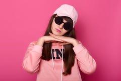Le beau jeune adolescent d'une chevelure foncé avec de grandes lunettes de soleil noires, hoody rose de port et chapeau, semble b photos libres de droits