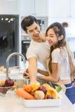 Le beau jeune couple asiatique regarde à la cuisson dans la cuisine Images stock