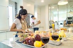 Le beau jeune couple asiatique regarde à la cuisson dans la cuisine Photo stock