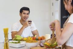Le beau jeune couple asiatique regarde à la cuisson dans la cuisine Photo libre de droits
