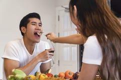 Le beau jeune couple asiatique regarde à la cuisson dans la cuisine Photographie stock