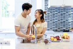 Le beau jeune couple asiatique regarde à la cuisson dans la cuisine Photographie stock libre de droits