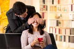 Le beau jeune couple dans l'amour, ami couvre les yeux de son girfriend à un arrière-plan de bureau Photographie stock