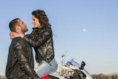 Le beau jeune couple dans l'amour est étreignant et embrassant sur une moto Photographie stock
