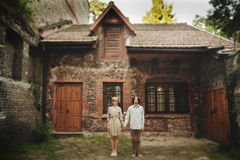 Le beau jeune couple de mariage se tient près de la vieille maison en bois Photos libres de droits