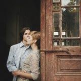 Le beau jeune couple de mariage se tient près de la vieille maison en bois Photos stock