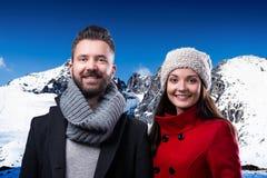 Le beau jeune couple en hiver vêtx en montagnes d'hiver Image stock