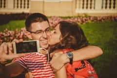 Le beau jeune couple est étreignant et prenant le selfie tout en se reposant ensemble en parc de fleur La fille embrasse son ami Photos libres de droits