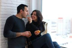 Le beau jeune couple examine la distance par le windo Photos stock