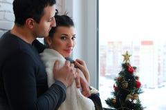 Le beau jeune couple examine la distance par le windo Photographie stock