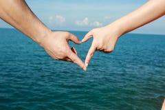 Le beau jeune couple fait le coeur avec les doigts photographie stock