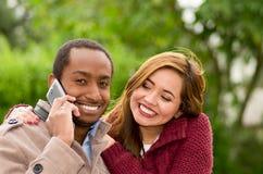 Le beau jeune beau couple multi-ethnique, la femme souriant à son ami et l'homme utilise son téléphone portable Photo stock