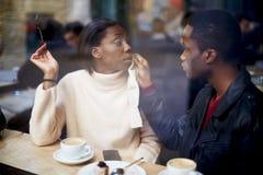 Le beau jeune couple se reposant dans le café et le type s'occupe tendrement de son amie Image stock