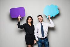 Le beau jeune couple tient des bulles de la parole, regarde l'appareil-photo et sourit, sur le fond gris Images stock