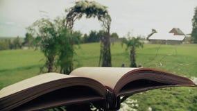 Le beau livre pour le mariage, préparé pour la célébration, les pages flottent dans le vent, à l'arrière-plan clips vidéos
