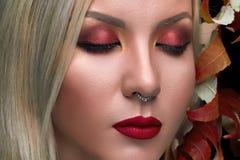 Le beau mannequin avec le maquillage rouge de lèvres, sèchent des feuilles Photo libre de droits