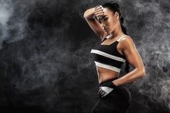 Le beau modèle afro-américain sportif, femme dans le sportwear fait la forme physique s'exerçant au fond noir pour rester convena photo stock