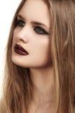 Le beau modèle avec de longs cheveux et les lèvres foncées grunges de lustre préparent, revêtement noir Photos stock