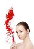 Le beau modèle avec la peinture de tube de rouge à lèvres éclabousse Photos libres de droits