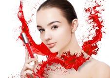Le beau modèle avec la peinture de tube de rouge à lèvres éclabousse Images libres de droits