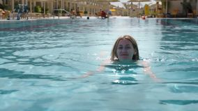 Le beau modèle caucasien, jeune femme nage dans une piscine avec de l'eau bleu dans un hôtel, sous le ciel ouvert Le concept banque de vidéos