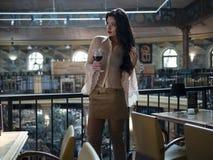 Le beau modèle de fille avec de longues jambes dans une jupe courte se tient avec un verre dans un restaurant photo stock