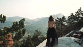 Le beau modèle de jeune femme avec de longs cheveux dans une longue robe élégante pelucheuse noire marche le long du balcon dans clips vidéos