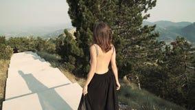 Le beau modèle de jeune femme avec de longs cheveux dans une longue robe élégante pelucheuse noire marche le long du balcon dans banque de vidéos