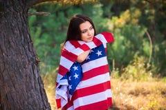 Le beau modèle pose avec le drapeau des Etats-Unis en parc d'été Images stock