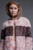 Le beau modèle roux posant dans le studio a tiré sur le fond gris Photographie stock libre de droits