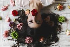 Le beau modèle sexy de brune se trouve sur le plancher avec les cheveux en désordre parmi des fleurs - vue d'en haut, à l'envers photos libres de droits