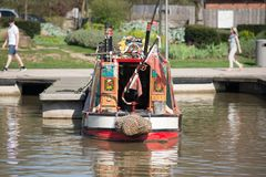 Le beau narrowboat brillamment coloré de péniche de canal a amarré en bassin de canal le jour ensoleillé au R-U Image libre de droits