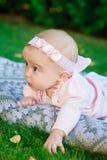 Le beau petit bébé se trouve sur une couverture de plaid Image stock