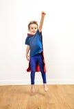 Le beau petit garçon enthousiaste s'est habillé comme sauter puissant de super héros image libre de droits