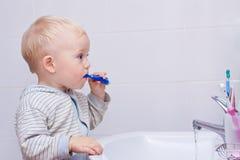 Le beau petit garçon nettoie ses dents Photos stock