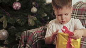 Le beau, petit garçon ouvre son cadeau de Noël clips vidéos