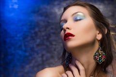 Le beau port de fille boucles d'oreille sur un backgr coloré d'aluminium Photographie stock