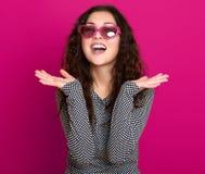 Le beau portrait de jeune femme, posant sur le fond rose, les longs cheveux bouclés, lunettes de soleil au coeur forment, concept photo libre de droits