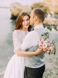 Le beau portrait des nouveaux mariés au fond de la mer Le marié embrasse la jeune mariée Images stock