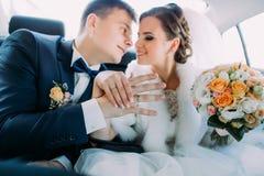 Le beau portrait des nouveaux mariés heureux montrant les mains avec les anneaux de mariage tout en se reposant dans la voiture Image stock
