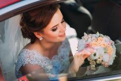Le beau portrait en gros plan de la jeune mariée tenant le bouquet de mariage tout en se reposant dans la voiture Images stock
