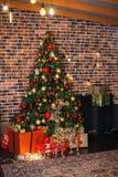 Le beau salon de Noël avec l'arbre de Noël, les cadeaux et les cerfs communs décorés avec rougeoyer s'allume la nuit An neuf photographie stock libre de droits