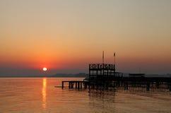 Le beau soleil et la silhouette de la plate-forme en bois au lever de soleil Photographie stock libre de droits