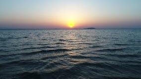 Le beau soleil plaçant au-dessus de l'océan avec la mer banque de vidéos