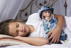 Le beau sommeil de petite fille dans un lit et étreignent son bébé - poupée Image libre de droits