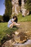 le beau touriste apprécie la nature à côté d'une rivière de montagne Photographie stock