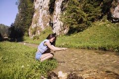 le beau touriste apprécie la nature à côté d'une rivière de montagne Image stock