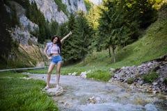 le beau touriste apprécie la nature à côté d'une rivière de montagne Photographie stock libre de droits