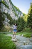 le beau touriste apprécie la nature à côté d'une rivière de montagne Images stock