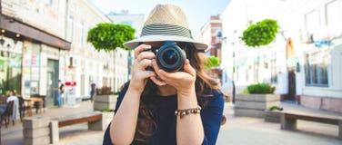 Le beau touriste de femme marchant sur la rue avec un appareil-photo et prend à des photos le concept en gros plan de bannière ex Photos stock